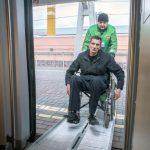 Сотрудник РЖД помогает пассажиру с инвалидностью сесть в вагон
